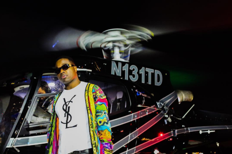Troy Ave stands in front of a helicopter.