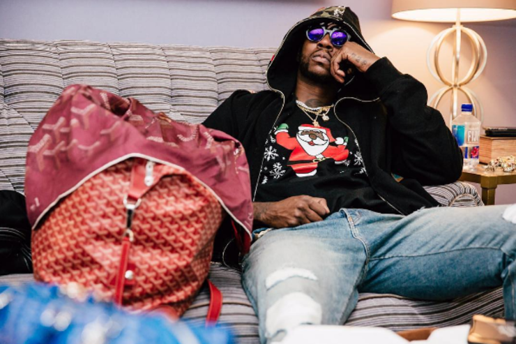 2 Chainz wearing one his ugly Christmas sweaters.