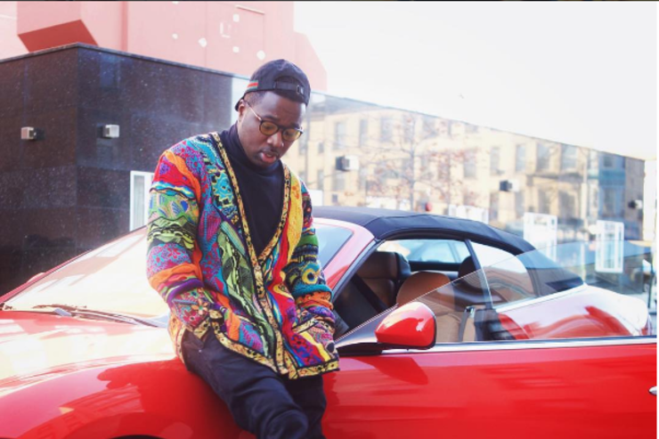 Troy Ave sitting on the hood of his sports car.