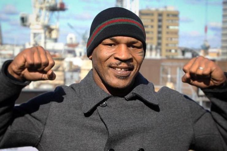 Mike Tyson flexes on a rooftop.