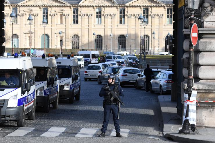 Police stand guard close to the Louvre museum in France.