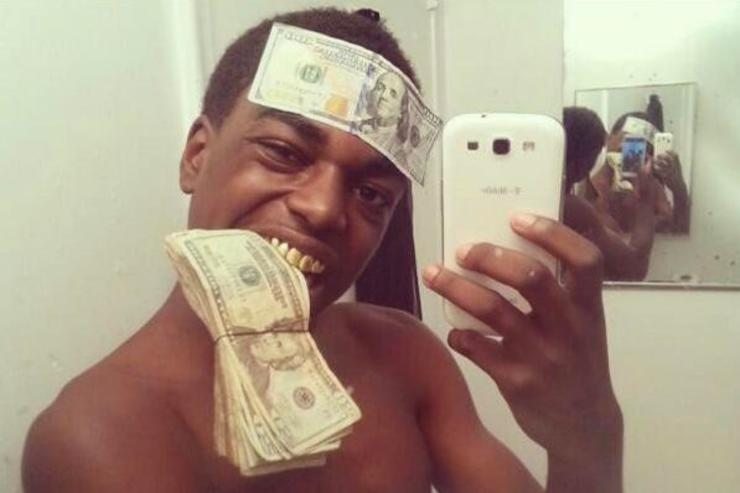 Kodak Black makes a selfie with a stack of  money between his teeth and a $100 bill stuck to his forehead.