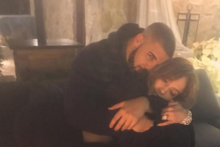 Drake and Jennifer Lopez cuddle on a couch.