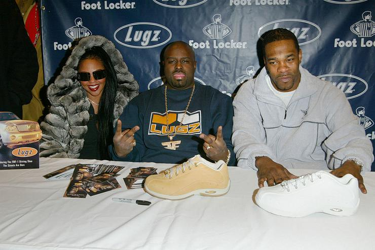 Hip hop artists (L to R) Lil' Kim, Funkmaster Flex and Busta Rhymes attend the launch of the Lugz/Funkmaster Flex FMF-1 Driving Shoe at a Foot Locker shoe store January 30, 2003 in New York City.
