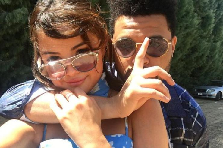 Selena Gomez and The Weeknd hug while posing for a picture.