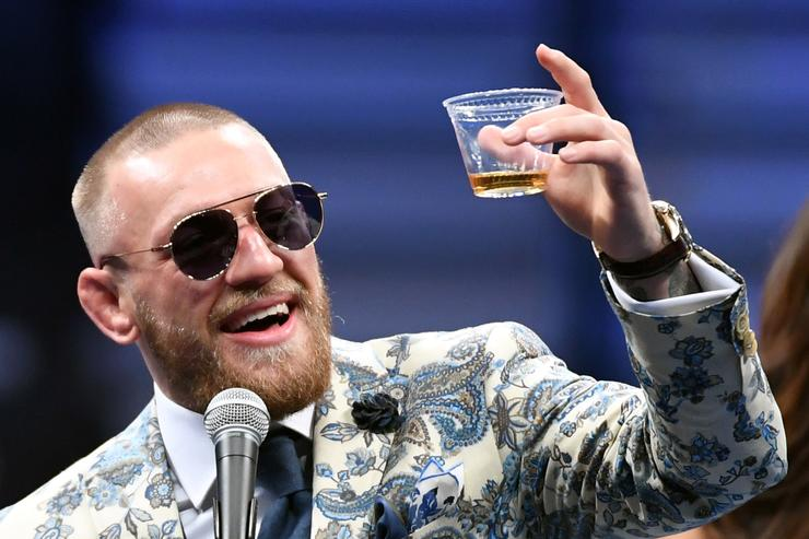 Conor McGregor holds up a cup of his Notorious-branded Irish whiskey as he speaks during a news conference following his 10th-round TKO loss to Floyd Mayweather Jr. in their super welterweight boxing match at T-Mobile Arena on August 26, 2017 in Las Vegas, Nevada.