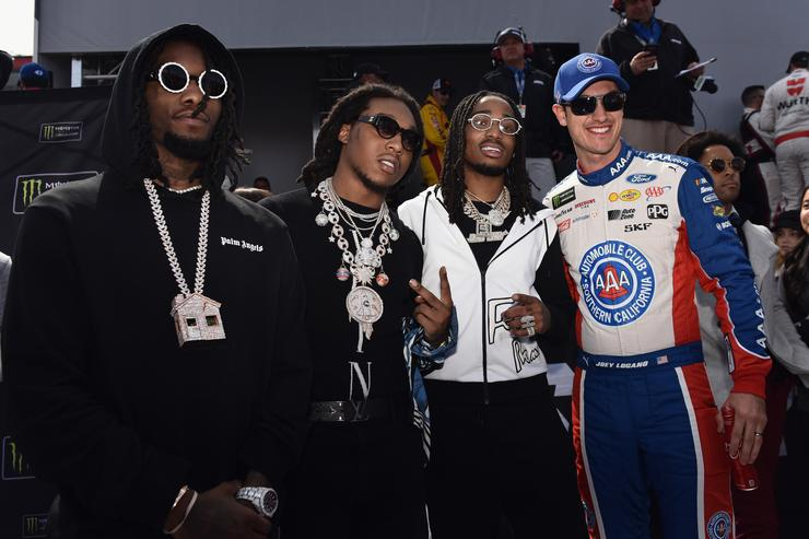 Joey Logano, driver of the #22 AAA Southern California Ford, meets Migos prior to the Monster Energy NASCAR Cup Series Auto Club 400 at Auto Club Speedway on March 18, 2018 in Fontana, California