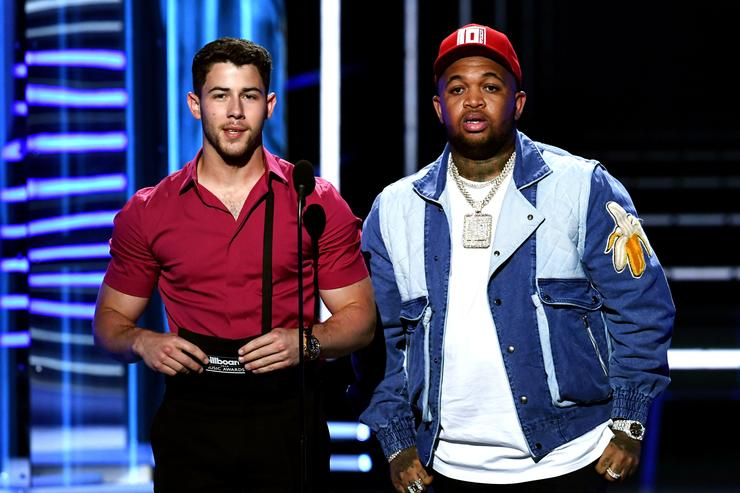 Recording artists Nick Jonas (L) and DJ Mustard speak onstage during the 2018 Billboard Music Awards at MGM Grand Garden Arena on May 20, 2018 in Las Vegas, Nevada.